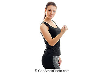 strong young brunette sport girl in black unform looking at...