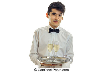 beautiful brunette male waiter with champagne on tray