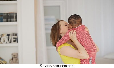 Happy Mom holding the baby in her arms - Mom holding the...