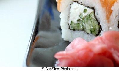 Japanese sushi on black plate.