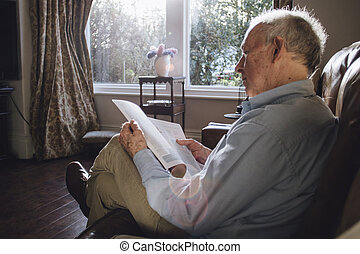 Reading The Paper - Senior man sitting alone in the living...