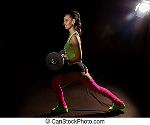 Fitness sexy girl with barbell on a dark background. Athlete doing exercises in the gym