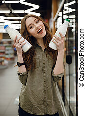 Vertical image of woman holding bottle milk - Vertical image...