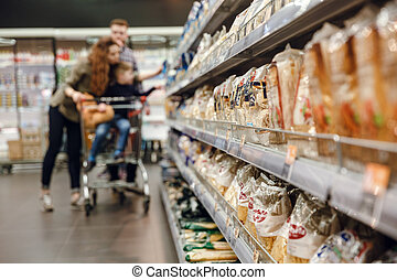 Photo of Supermarket with family on background. Blur image
