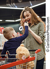 Vertical image of young boy showing candy to his mother -...