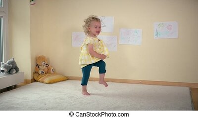 Mischievous girl running jumping and falling on white carpet...