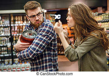 Angry woman trying to take away from man keg beer - Angry...