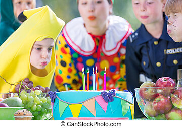 Kids on a dressing up party - Happy kids blowing the candles...