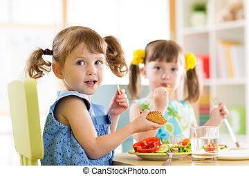 Children eating from plates in day care centre - Children...