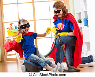 Child and mother dressed as superheroes using vacuum cleaner in room. Family middle-aged woman and daughter have a fun while cleaning the floor.