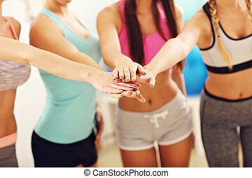 Young women group gicing high five at the gym after workout