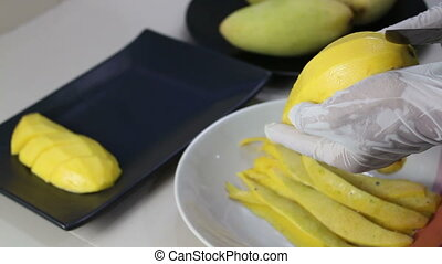 Hands cutting mango with knife