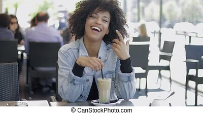 Lovely young woman with drink - Young black woman in denim...