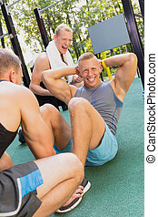 Man doing sit-ups - Muscular young man doing sit-ups and his...