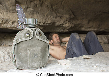 Water canteen and army man resting in cave - U.S. green...
