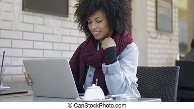 Smiling woman browsing laptop in cafe - Attractive African...