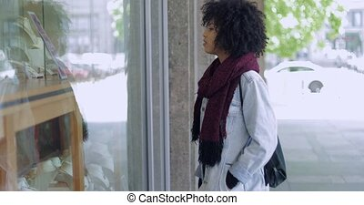 Young woman looking at window of shop - Side view of black...