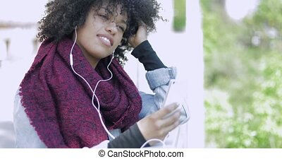 African female with headphones and phone posing - Young...
