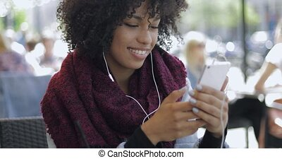 African woman with smartphone in cafe - Young black woman in...