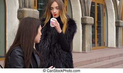 two cute girl talking and drinking coffee on the street at...