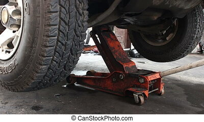 Mechanic Lowers Truck On Floor Jack