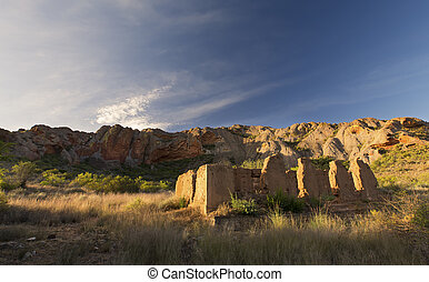 Ruins of old house with a mountain and clouds in the background
