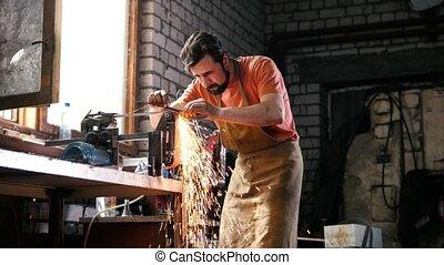 Grinding metal tools with sparkles - forge workshop, slider...