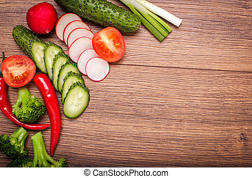 tomato, radish, cucumber, broccoli, onion, chili on a wooden surface. arrangement of sliced vegetables. Top view with copy space for text. Top view with copy space for text