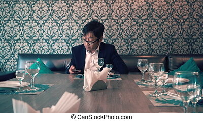 Asian man in suit businessman waiting in the cafe their food. Long waits for ordering. Nervous