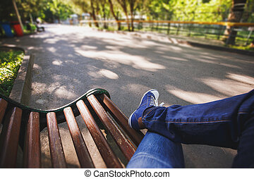 First-person view a man sitting on wooden bench in the park.