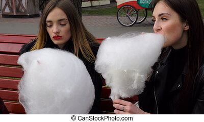 two funny girlfriend eat cotton candy on the street and...