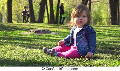 Little baby girl in the park in summer
