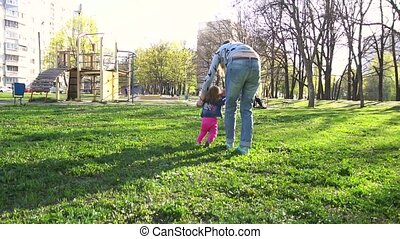 Mother teaching her baby first steps in the park