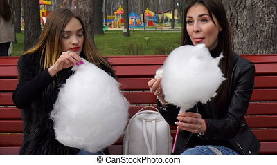 charming girls sit on a bench and eat cotton candy outdoors
