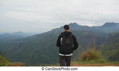 Young male hiker with backpack reaching up top of mountain...