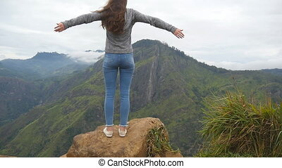 Young girl reaching up top of mountain and raised hands....