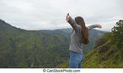 Woman tourist standing on the edge of beautiful canyon, victoriously outstretching arms up. Young female hiker reaching up top of mountain and raised hands. Slow motion