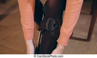 Lady Putting On Supportive Leg Brace - Detail of the lower...