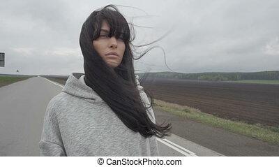 Woman walking on empty rural road