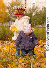 Children playing in autumn - Girls with maple leaves playing...