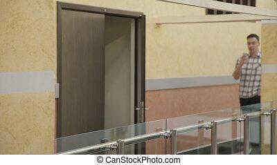 Man walk along hall in business center speaking smartphone....