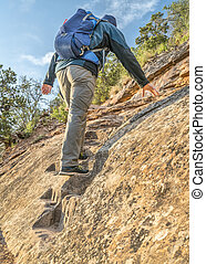Hiker on a steep trail in Rocky Mountains - Male hiker...