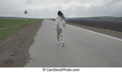 Woman running on empty rural road