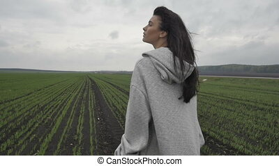 Woman walking in field with eyes closed - Side view of...