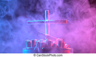 Smoldering cross of cigarettes. - Smoldering cross of...