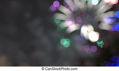 Slow motion of colorful bokeh lights circles from new year celebration fireworks on night city street. Abstract background