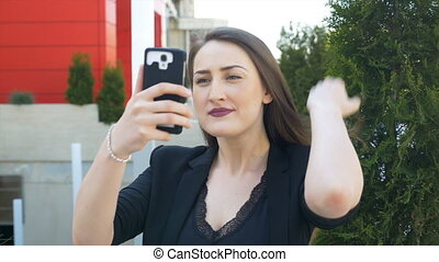 Beautiful woman checking her makeup and hair using camera of smartphone before taking selfie