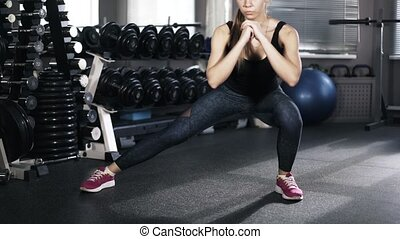 Young woman doing leg exercise in a gym - Front view of a...