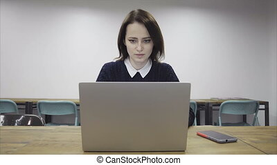 Serious woman using a laptop