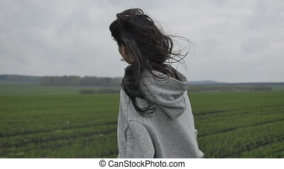 Woman in field with flying hair